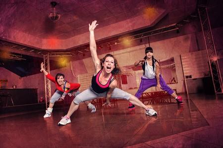 salle de fitness femmes qui sourient et dansent la zumba